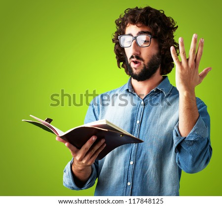 Portrait Of Man Reading Book against a green background - stock photo