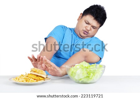 Portrait of man refuse to eat junk food and choose a bow of salad - stock photo