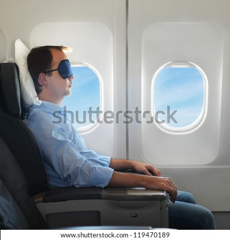 Portrait of man relaxing in sleaping mask in the airplane