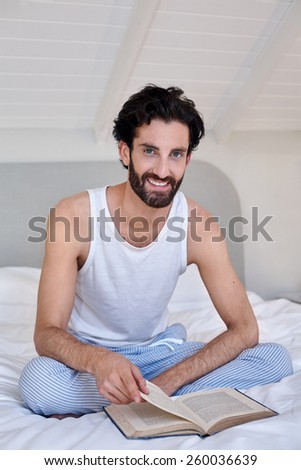 portrait of man relaxing on bed reading literature novel story book at home