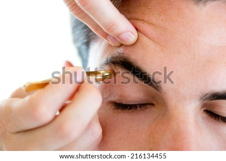 Portrait of man removing eyebrow hairs with tweezing. - stock photo