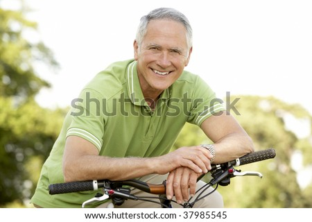 Portrait of man riding cycle in countryside - stock photo