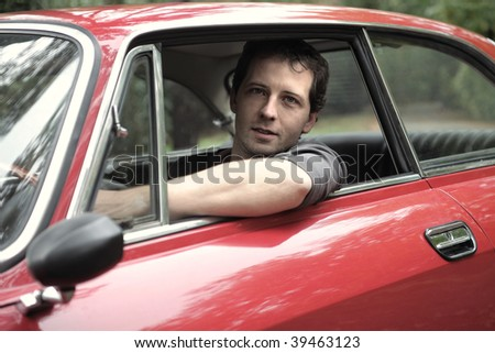 portrait of man seated in a vintage car - stock photo