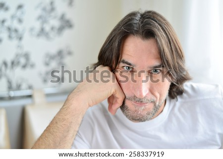 Portrait of man sitting in a living room - stock photo