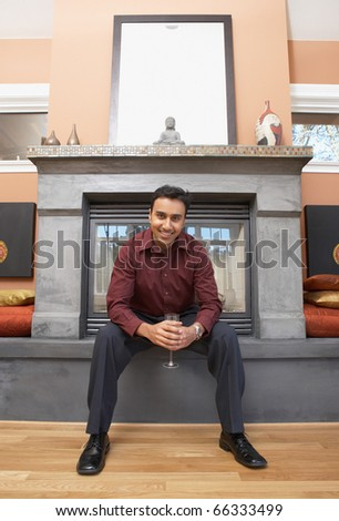 Portrait of man sitting in front of fireplace