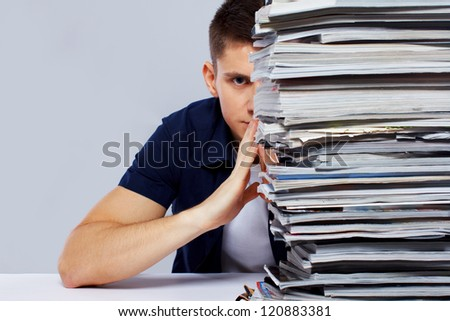 Portrait of man sitting in front of magazines - stock photo