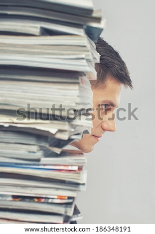 Portrait of man sitting in front of magazines