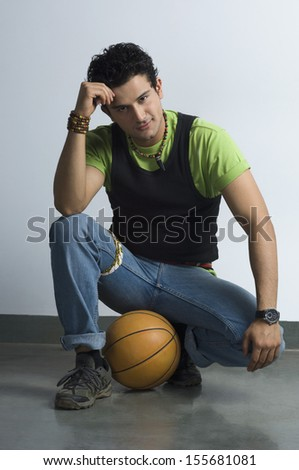 Portrait of man sitting with a basketball