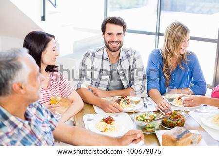 Portrait of man sitting with friends at dinning table while having meal - stock photo