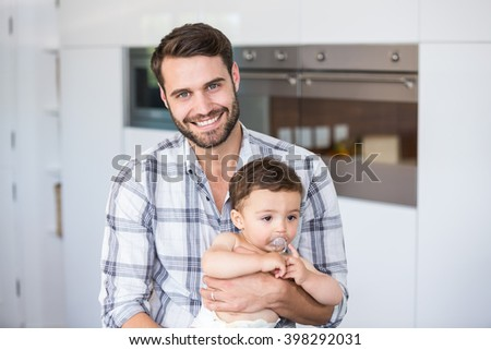 Portrait of man smiling while carrying son at home - stock photo