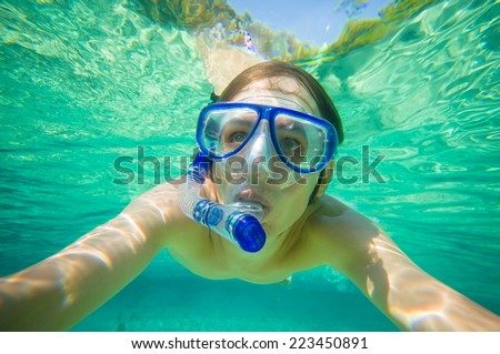 Portrait of man snorkeling in crystal clear lagoon water on tropical island