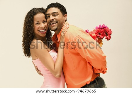 Portrait of man surprising girlfriend with flowers - stock photo