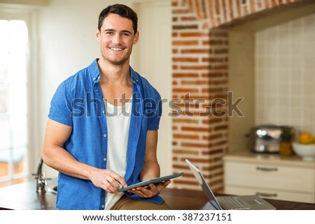 Portrait of man using digital tablet with laptop in kitchen - stock photo