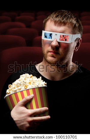 Portrait of man watching 3D movie and holding bucket of popcorn