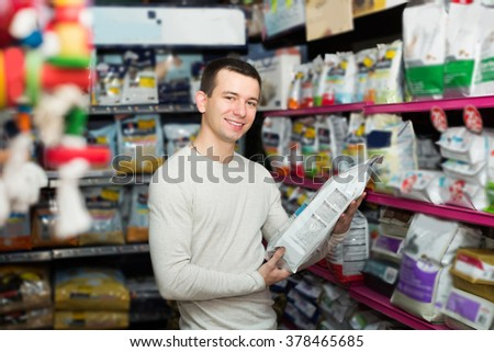 Portrait of man watching diet products and smiling in pet store - stock photo