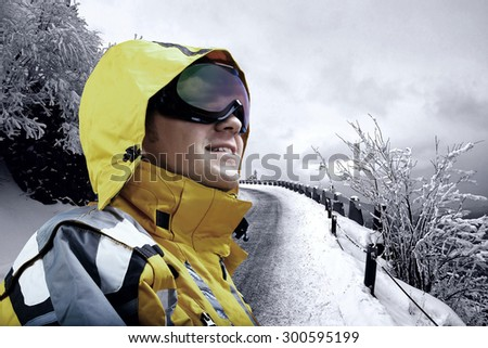 Portrait of man wearing a helmet and glasses on the background of snow winter and mounts.