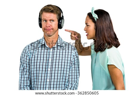 Portrait of man wearing headphones with woman shouting beside him - stock photo