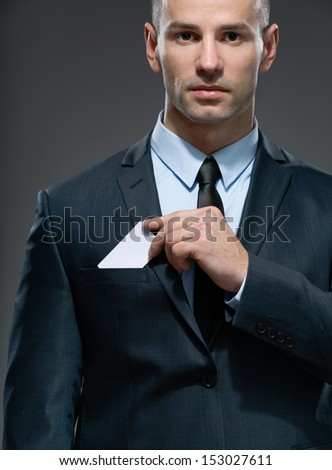 Portrait of man who pulls out business card from the pocket of business suit, copyspace