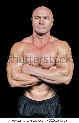Portrait of man with arms crossed against black background - stock photo