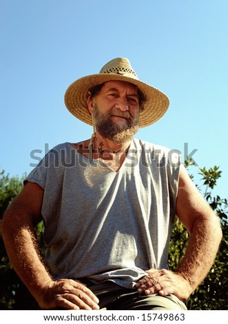 portrait of man with beard and star tattoos in straw hat