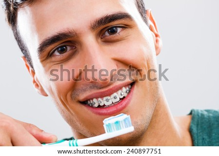 Portrait of man with braces holding toothbrush,Dental hygiene - stock photo