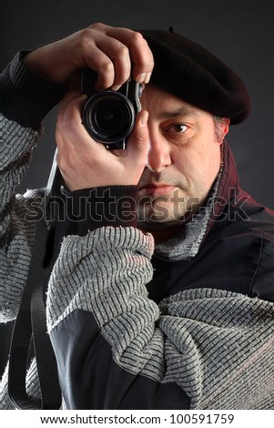 Portrait of man with camera over black - stock photo