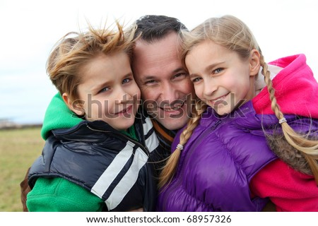 Portrait of man with 2 children out in the countryside - stock photo