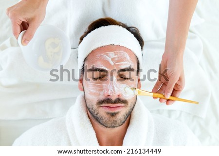 Portrait of man with clay facial mask in beauty spa.  - stock photo