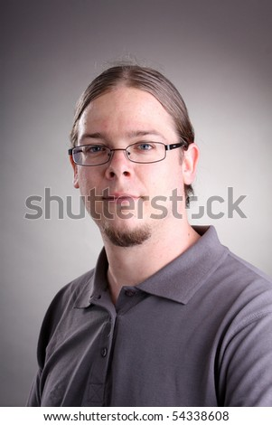 portrait of man with long hair and eyeglass
