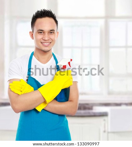 Portrait Of Man With Sprayer Ready To Do Housework In The Kitchen