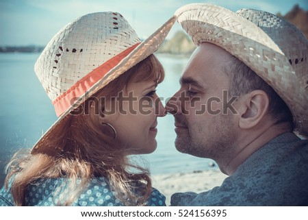 Portrait of man with woman sitting on the beach and looking to each other