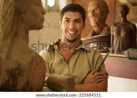 Portrait of man working, young student in art class, learning crafts profession, working with wooden statue and looking at camera - stock photo