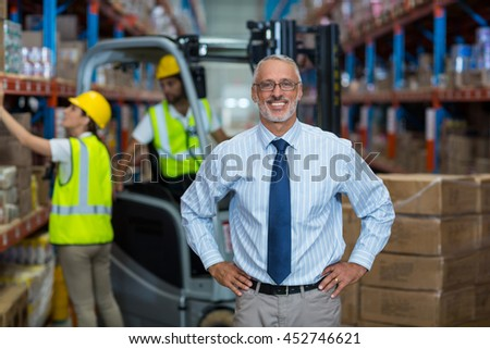 Portrait of manager is smiling and posing with hands on hips in warehouse