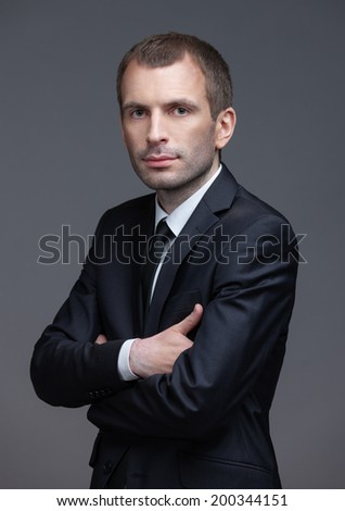 Portrait of manager with crossed hands, isolated on grey background. Concept of leadership and success