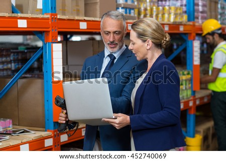 Portrait of managers are looking a laptop in a warehouse
