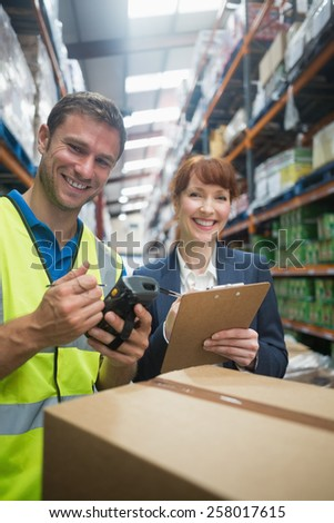 Portrait of manual worker and manager scanning package in the warehouse - stock photo