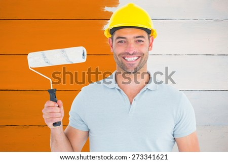 Portrait of manual worker holding paint roller against painted blue wooden planks - stock photo