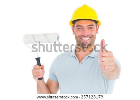 Portrait of manual worker with paint roller gesturing thumbs up on white background - stock photo