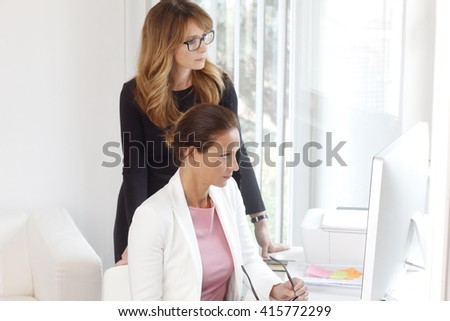 Portrait of marketing team working together on new project and consulting in front of computer at office.  - stock photo