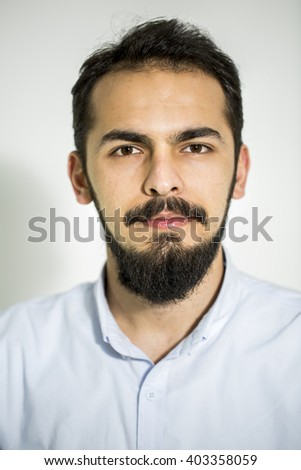 Portrait of masculinity.Portrait of handsome young bearded man looking at camera while standing against white background.The man with a big beard and moustaches.An image of a handsome man with a beard
