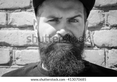 Portrait of masculinity. Portrait of handsome young bearded man looking at camera while standing against grey background