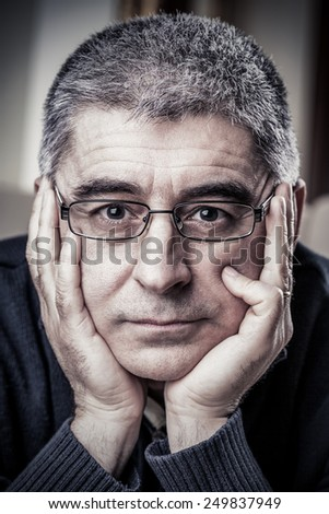 Portrait of mature adult Caucasian man with sorrow expression holding his face in his hands. - stock photo