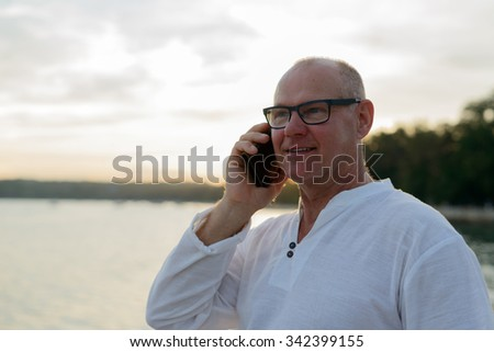 Portrait of mature adult man outdoors talking on phone