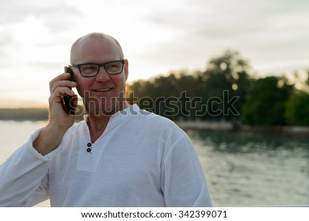 Portrait of mature adult man outdoors using mobile phone