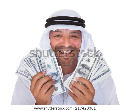 Portrait Of Mature Arab Man Holding Dollars Over White Background - stock photo