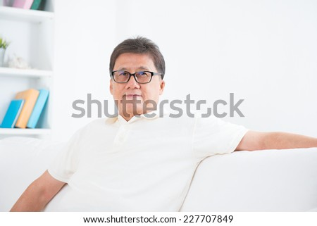 Portrait of mature Asian man smiling, sitting on sofa at home, senior retiree indoors living lifestyle.  - stock photo