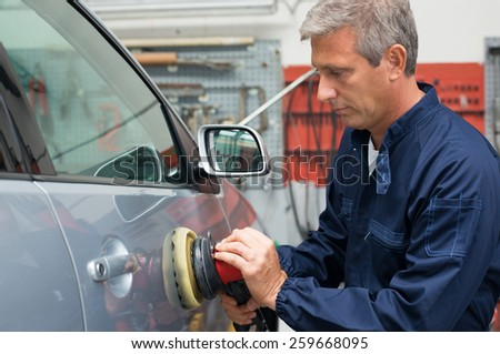 Portrait Of Mature Auto Mechanic Polishing Car At Workshop - stock photo