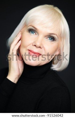Portrait of mature blond female looking at camera - stock photo