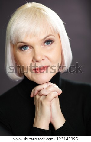 Portrait of mature blond female looking at camera on black background - stock photo