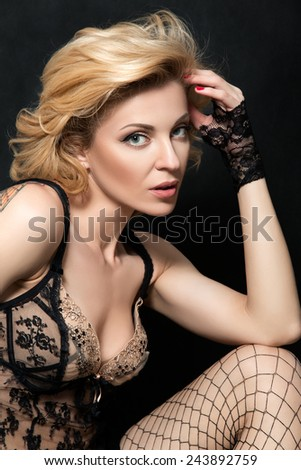 Portrait of mature blonde sensual woman in sexy linen touching her hair - stock photo
